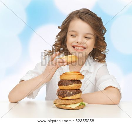 junk food, unhealthy eating, children and people concept happy smiling girl eating buns, donuts and burger over blue lights background