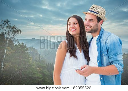 Happy hipster couple smiling together against trees and mountain range against cloudy sky