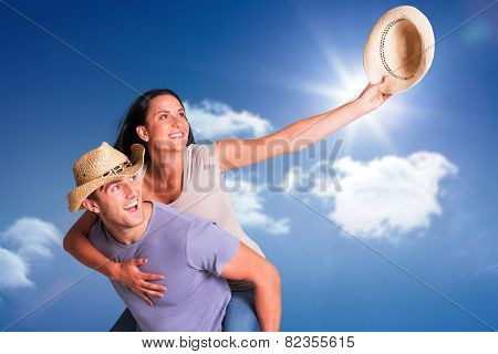 Man giving his pretty girlfriend a piggy back against bright blue sky with clouds
