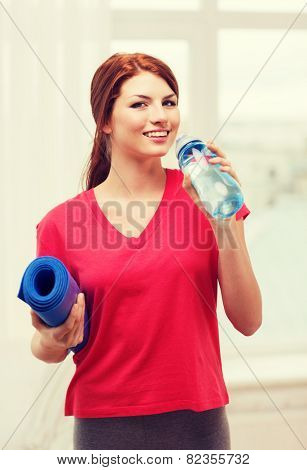 fitness, home and diet concept - smiling teenage girl with bottle of water and yoga mat after exercising at home