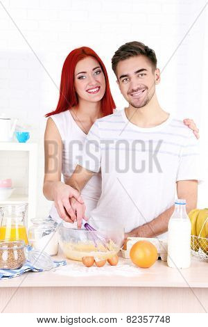 Happy couple cooking in kitchen