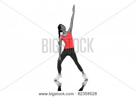 Full length of a sporty young woman stretching hand against mirror