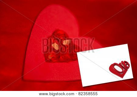 Rubies and paper red heart against white card
