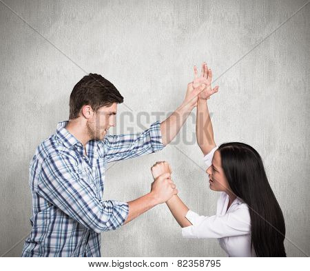 Aggressive man overpowering his girlfriend against weathered surface
