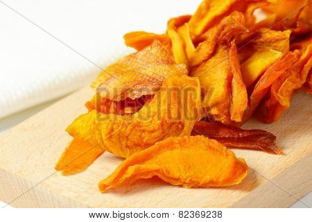 heap of dried mango slices on wooden cutting board