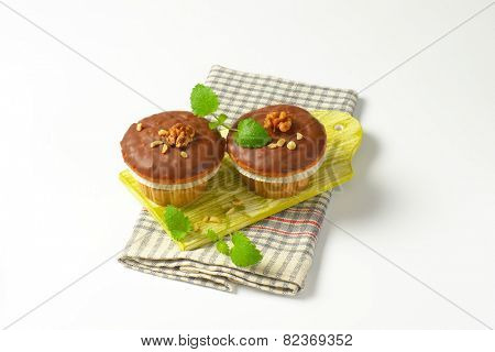 two chocolate muffins on green cutting board and checkered dishtowel