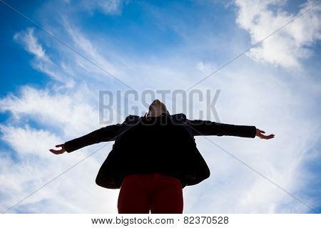 Young woman spreading arms towards the blue sky