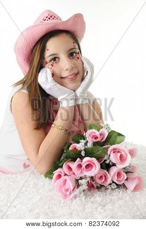 Closeup of a beautiful teen girl in formal gloves and a pink cowgirl hat.  Her face is adorned with sparkly red and pink hearts.  On a white background.