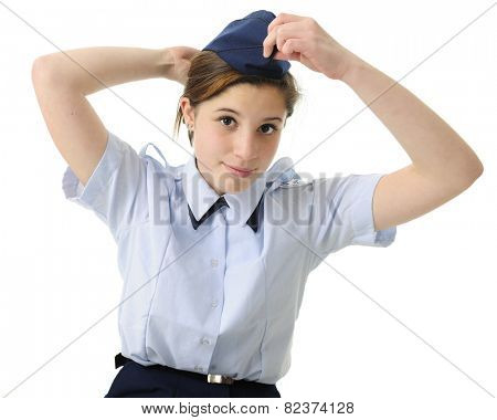 An attractive teen girl putting on her navy blue ROTC hat.  On a white background.