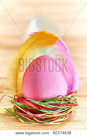 Painted Easter Egg in colorful nest on wooden background