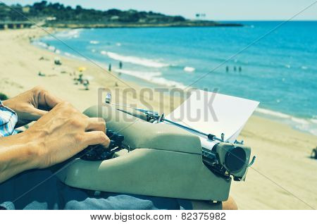 a young man typing in an old typewriter on the beach