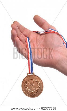 Athlete hand holding gold medal.Award winner hand holding a gold medal isolated on white background.