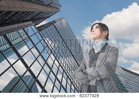 Confident Asian business woman stand and think, closeup portrait with office building background.