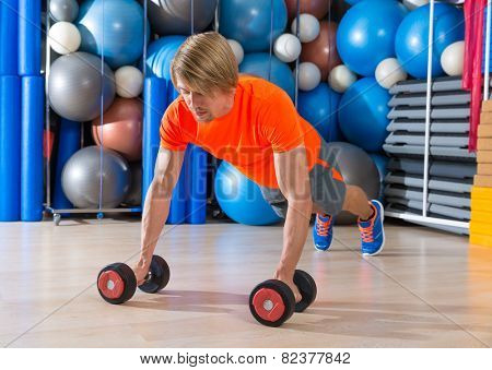 Blond man gym push-up strength pushup exercise with dumbbells workout