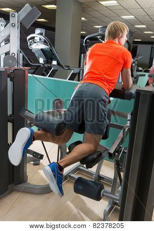 Kneeling leg femoral curl man exercise at gym rear view workout