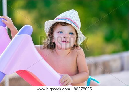 Baby kid girl with hat in summer on green field background