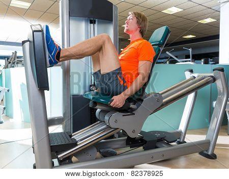 Gym seated leg press machine blond man workout at indoor