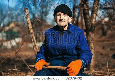 Old Man In Workwear Sitting Outdoors With Axe