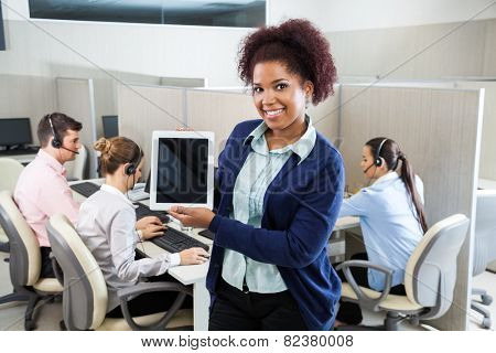 Portrait of confident female customer service agent displaying tablet computer while colleagues working in background at call center