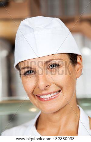 Closeup portrait of mature female butcher smiling in butchery