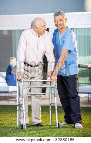 Portrait of smiling caretaker assisting senior man to use walking frame at nursing home lawn