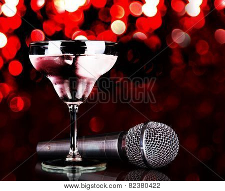 Silver microphone and cocktail on table on red lights background
