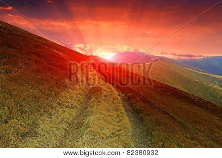 Sunset in mountains over rut road