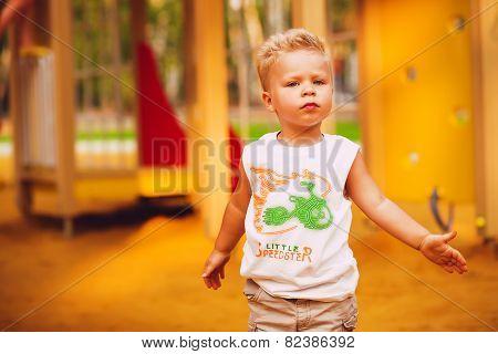 Blond Cute Boy On Playground