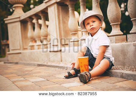 Boy Sitting On Sett Near Balustrade