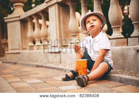 Cute Boy In Hat Sitting On Sett