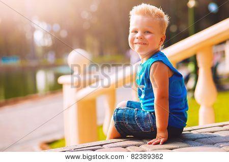Happy Boy Sitting On Sett Near Balustrade
