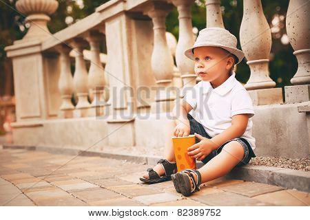 Little Boy In Hat Sitting Near Balustrade