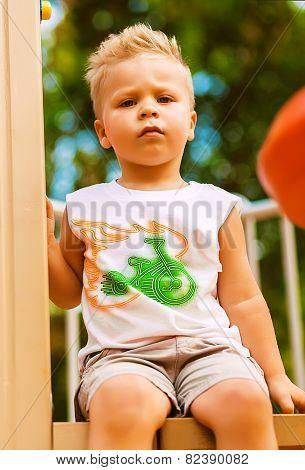 Serious Blond Boy Sitting On Playground