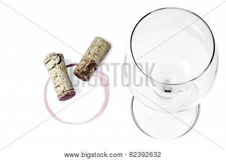 An empty wine glass, corks and a wine imprint on a white background