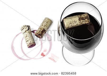 A wine glass, corks and a wine imprint on a white background