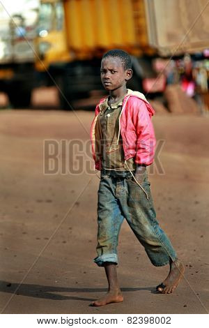 Dark Skinned African Boy Walking Barefoot In Dirty Jeans.