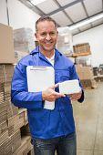 stock photo of warehouse  - Smiling warehouse worker holding small box and clipboard in a large warehouse - JPG