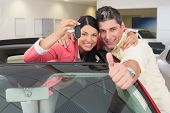 image of showrooms  - Smiling couple giving thumbs up and holding car key at new car showroom - JPG