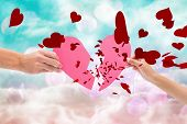 foto of girly  - Hands holding two halves of broken heart against digitally generated pink and blue girly design - JPG