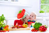 stock photo of twin baby girls  - Two little children adorable toddler girl in red chef hat and apron and funny baby boy preparing healthy lunch making delicious salad with fresh vegetables and garden herbs in a white sunny kitchen - JPG