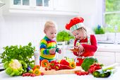 picture of baby twins  - Two little children adorable toddler girl in red chef hat and apron and funny baby boy preparing healthy lunch making delicious salad with fresh vegetables and garden herbs in a white sunny kitchen - JPG