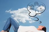 stock photo of cloudy  - Young woman lying on floor thinking against cloudy sky - JPG