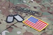 stock photo of army  - us army camouflaged uniform with US flag patch and blank dog tags - JPG