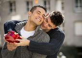 stock photo of gay couple  - young cool gay men couple on street with rose flower and heart shape box present giving gift celebrating valentines day in love on street urban background - JPG