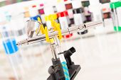 stock photo of airbrush  - Professional airbrush on a stand with colorful paints in backgroung - JPG
