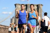 Постер, плакат: City running couple jogging outside Runners training outdoors working out in Brooklyn with Manhatta