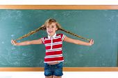 stock photo of braids  - Braided student blond girl playing in green chalkboard with braids at school classroom - JPG
