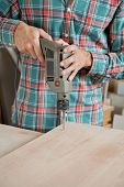 foto of workbench  - Midsection of carpenter drilling wood at workbench in workshop - JPG