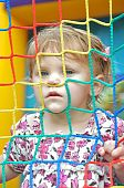 stock photo of bounce house  - pretty young girl with face pushed up to the ropes in a bouncy house - JPG