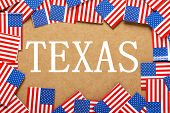 image of texas flag  - Miniature flags of the United States of America form a border on brown card around the word Texas - JPG